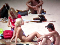 The cute blonde amateur is on this pure nudism video stretching the great natural body on the golden sand of the beach